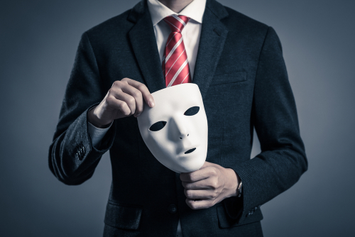 Businessman in suit from the neck down holding a white mask near his chest.