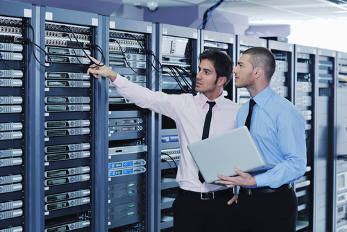 Two male technicians in business attire work in the server room.