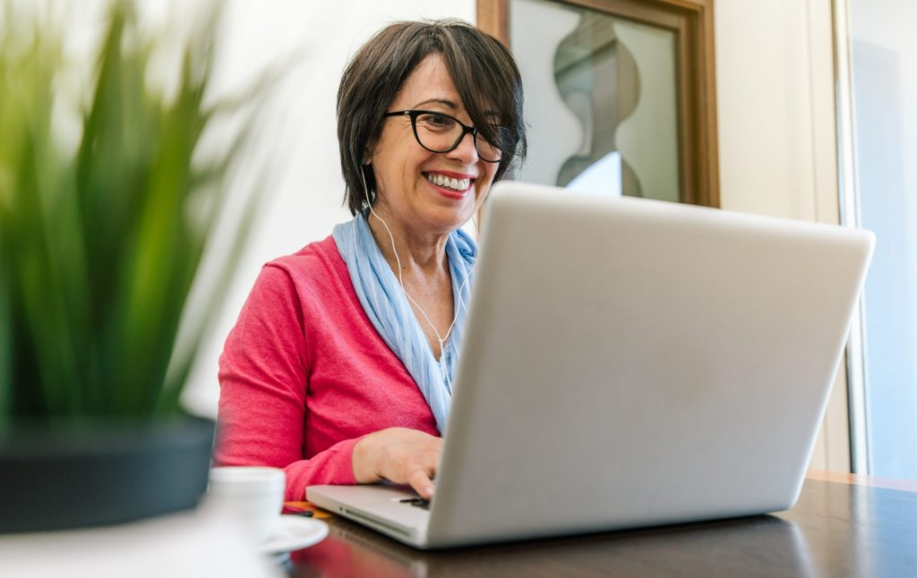 Woman with brown hair and glasses works from home on her laptop computer.
