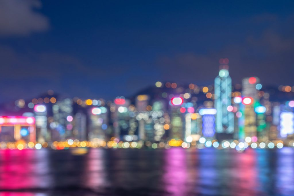 Blurred, abstract view of Hong Kong skyline brightly illuminated at night, reflected in water.