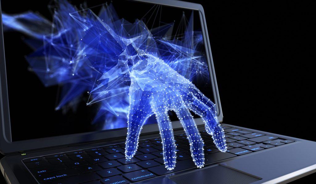 Digital hand reaches through laptop computer monitor to type on keyboard, representing cybersecurity threat.